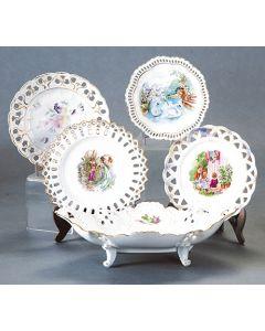2003-Lote en porcelana esmaltada centroeuropea formado por cuatro bandejitas circulares con ala calada y campo decorado con flores y personajes y cestita del mismo estilo.